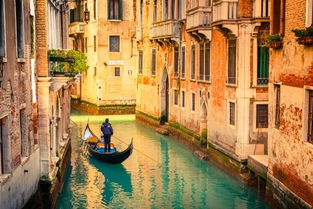 Gondola on narrow canal in Venice, Italy photo