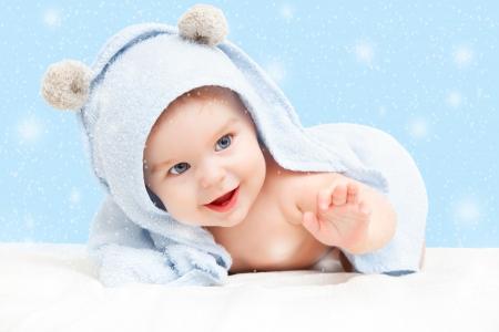 Sourire bébé avec une serviette sur fond d'hiver Banque d'images