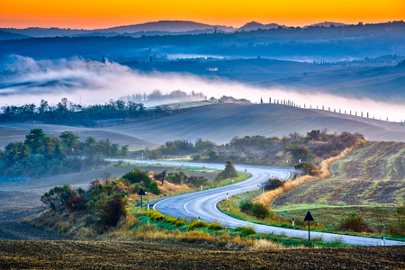 Tuscany foggy landscape at sunrise, Italy Stock Photo