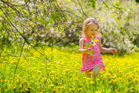 Little girl playing in the spring park