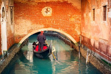 iconic: Gondola on narrow canal in Venice, Italy