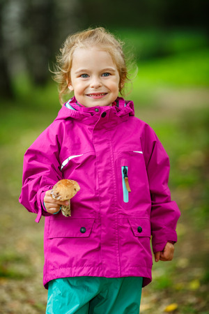 Happy little girl with a mushroom photo