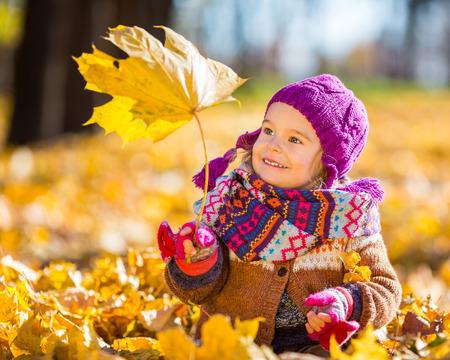 Kleine Mädchen spielen mit Herbstlaub Standard-Bild