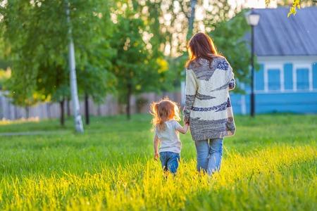niños caminando: Madre y pequeña hija caminando en el parque soleado