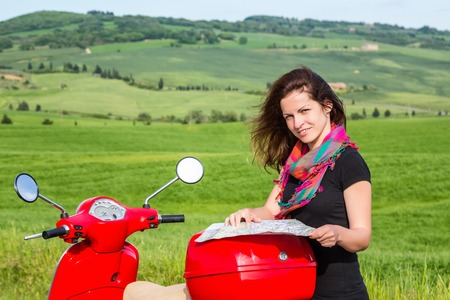 Young woman traveling by a scooter photo