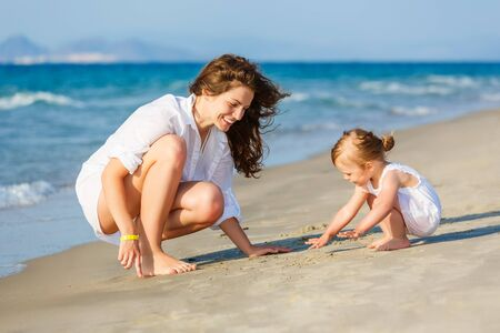playing in the sea: Mother and daughter playing on the beach