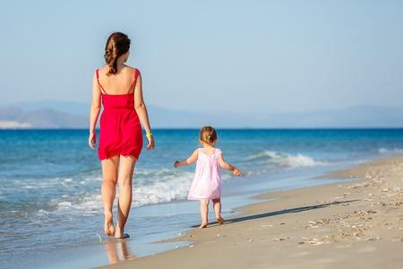 ni�o corriendo: Madre e hija en la playa Foto de archivo