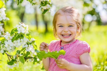 outside: Happy little girl in spring sunny park