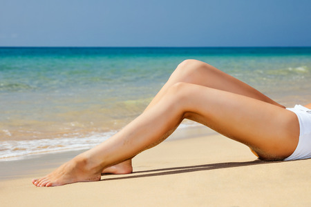 Womans  legs on the beach photo