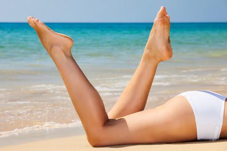 Womans benen op het strand