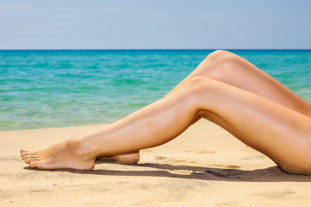 vacaciones en la playa: Womans piernas en la playa