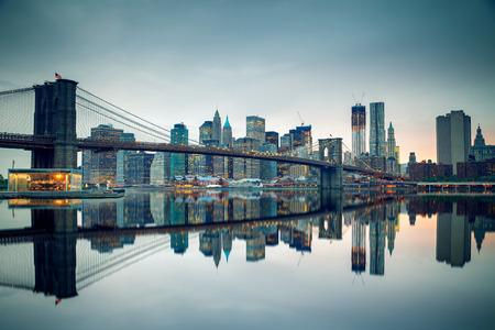 De brug van Brooklyn en Manhattan bij schemer