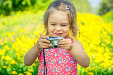 Little girl taking pictures on a meadow photo