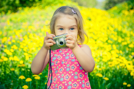 Little girl taking pictures on a meadow 스톡 콘텐츠