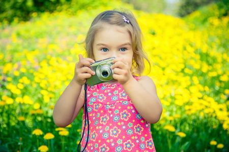 Little girl taking pictures on a meadow Foto de archivo