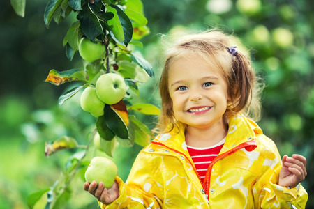 foliage: Happy little girl holding apple in the garden
