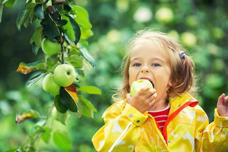 comiendo frutas: Niña que come la manzana fresca en el jardín