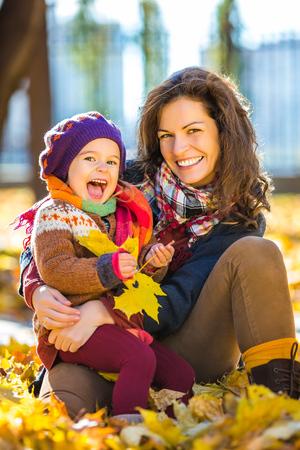 familia abrazo: Niña y su madre que juegan en el parque del otoño Foto de archivo