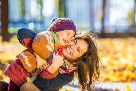riendo: Niña y su madre que juegan en el parque del otoño Foto de archivo