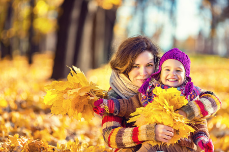 vibrant colors fun: Little girl and her mother playing in the autumn park