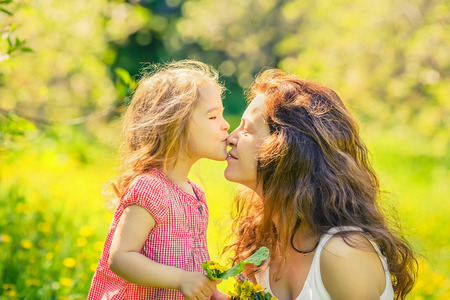 flowers white: Mother and daughter in spring sunny park Stock Photo