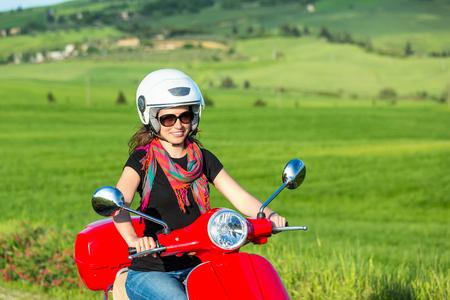 scooter: Mujer hermosa joven que viaja en una moto en la Toscana