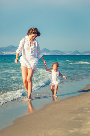 white woman: Mother and little daughter walking on the beach