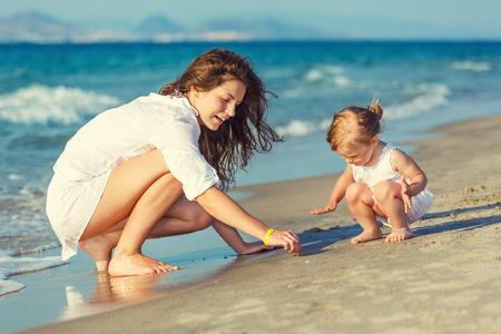 Moeder en dochter spelen op het strand