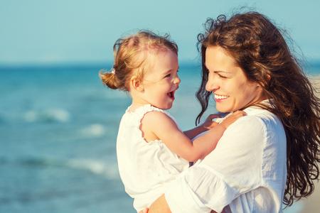 Retrato de la madre y su pequeña hija en la playa