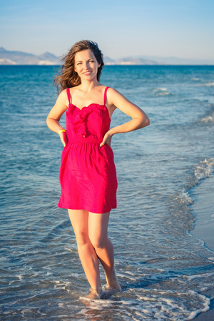 red and blue: Attractive young woman walking on the beach