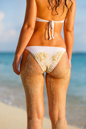 white water: Back of young woman in bikini standing on the beach Stock Photo
