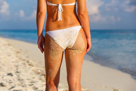 Back of young woman in bikini standing on the beach Stock Photo