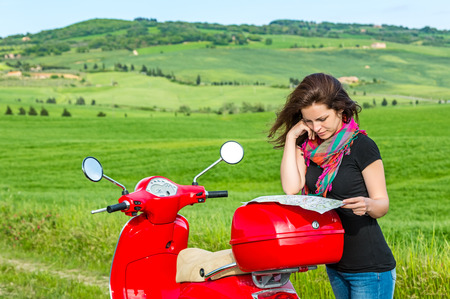 an adult person: Young beautiful woman traveling by a scooter in tuscany
