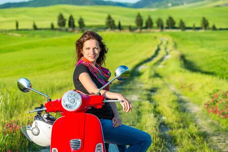 modern girls: Portrait of toung beautiful woman with a scooter and tuscany landscape in background