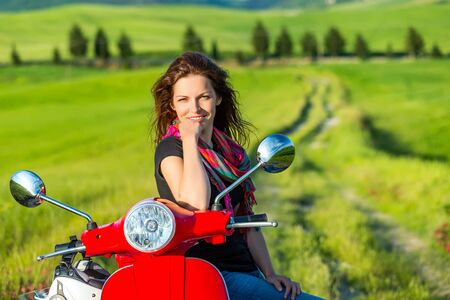 an adult person: Portrait of toung beautiful woman with a scooter and tuscany landscape in background