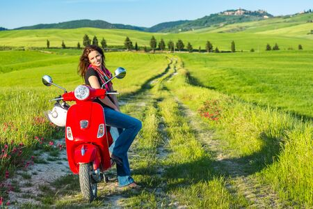 modern girl: Portrait of toung beautiful woman with a scooter and tuscany landscape in background