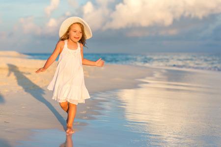 small girl: Little girl walking on beautiful ocean beach Stock Photo