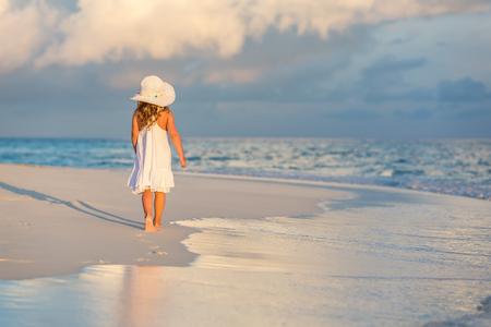 petite fille avec robe: Petite fille marchant sur la belle plage de l'océan Banque d'images