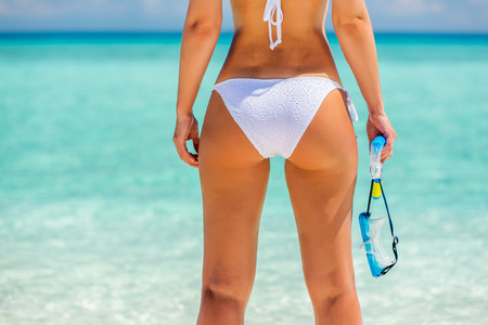sexy female: Back of young woman in bikini standing on the beach Stock Photo