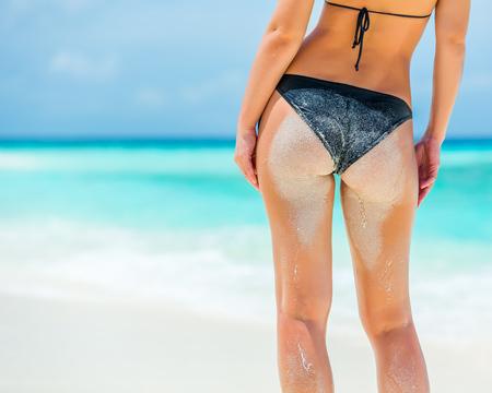 mojada: Detrás de la mujer joven en bikini de pie en la playa