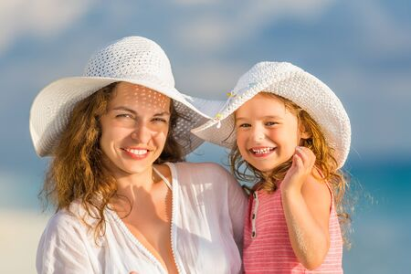 white hat: Portrait of mother and little daughter on the beach