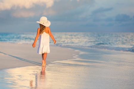 Petite fille marchant sur la belle plage de l'océan Banque d'images