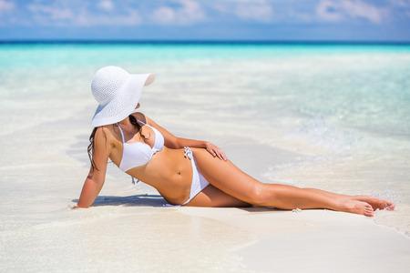 Young woman in bikini relaxing on the beach 스톡 콘텐츠