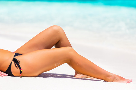 bare girl: Beautiful womans legs on the beach sand