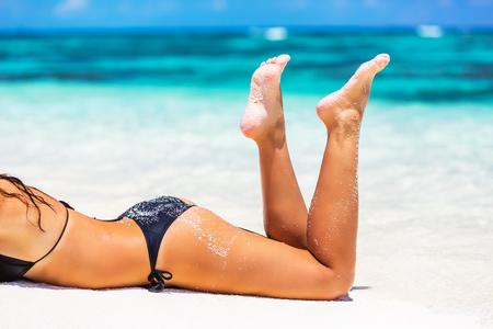 mujeres de espalda: piernas de la mujer hermosa en la arena de la playa