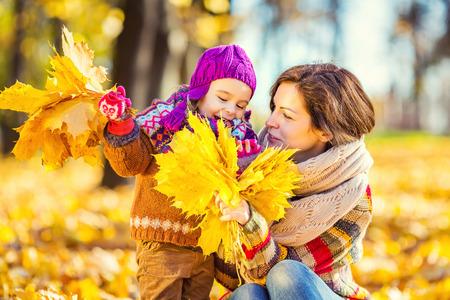 어린 소녀와 그녀의 어머니는 가을 공원에서 놀고 스톡 콘텐츠