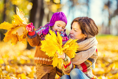 Little girl and her mother playing in the autumn park Фото со стока - 60208050