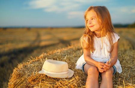 field sunset: Little girl in a field with hay rolls at sunset Stock Photo