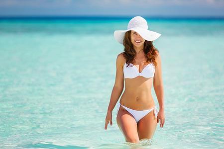 Aantrekkelijke jonge vrouw die op het strand loopt