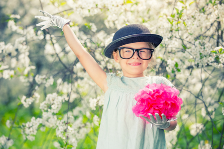 Funny girl in glasses, hat and gloves playing in spring garden. Stock Photo